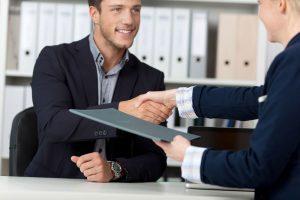 deux personnes se serrent la main de part et d'autre d'un bureau